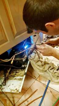 Man repairing water heater with welding techniques